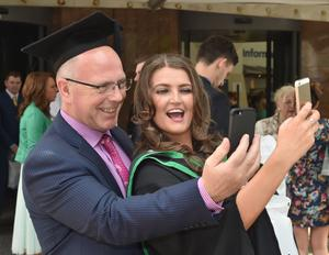 Ulster University Graduations-Waterfront Hall 03-07-15 Ashleigh Scott who graduated with Technology with Design gets a selfie with her father John Scott Photo by Simon Graham/Harrison Photography