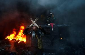 A protester gestures with the arms of a broken mannequin, during clashes with police in central Kiev, Ukraine, Thursday Jan. 23, 2014. Thick black smoke from burning tires engulfed parts of downtown Kiev as an ultimatum issued by the opposition to the president to call early election or face street rage was set to expire with no sign of a compromise on Thursday. (AP Photo/Sergei Grits)