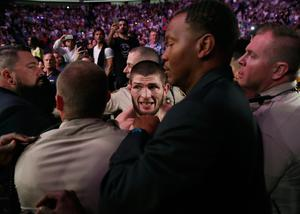 Khabib Nurmagomedov, center, is held back outside of the cage after fighting Conor McGregor in a lightweight title mixed martial arts bout at UFC 229 in Las Vegas, Saturday, Oct. 6, 2018. Nurmagomedov won the fight by submission during the fourth round to retain the title. (AP Photo/John Locher)