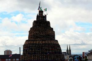 Loyalists gesture from the top of one of the largest 11th night Bonfires after raising Irish tricolour flags in the lower Shankill road area of Belfast, Northern Ireland on July 11, 2016, ahead of the lighting of the traditional 11th night bonfires. The Eleventh Night refers to the night before the Twelfth of July, an annual Protestant commemoration of the famous battle were Protestant King William III of Orange defeated Catholic King James II at the battle of the Boyne on July 12, 1690. / AFP PHOTO / PAUL FAITHPAUL FAITH/AFP/Getty Images