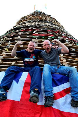 Loyalists gesture at the foot of one of the largest 11th night Bonfires after raising Irish tricolour flags in the lower Shankill road area of Belfast, Northern Ireland on July 11, 2016, ahead of the lighting of the traditional 11th night bonfires. The Eleventh Night refers to the night before the Twelfth of July, an annual Protestant commemoration of the famous battle were Protestant King William III of Orange defeated Catholic King James II at the battle of the Boyne on July 12, 1690. / AFP PHOTO / PAUL FAITHPAUL FAITH/AFP/Getty Images