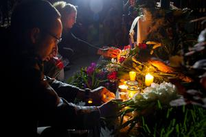 People place candles at the French embassy in Guatemala City, during a ceremony Sunday, Nov. 15, 2015, in homage to the victims of the deadly attacks in Paris. Multiple terrorist attacks across Paris on Friday night left more than one hundred dead and many more injured. (AP Photo/Moises Castillo)