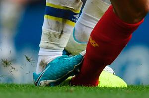 A close up view of Everton's English midfielder Ross Barkley's boot catching Liverpool's Croatian defender Dejan Lovren (R), Barkley  was subsequently booked for the challenge during the English Premier League football match between Liverpool and Everton at Anfield in Liverpool, north west England on April 1, 2017. / AFP PHOTO / Paul ELLIS / RESTRICTED TO EDITORIAL USE. No use with unauthorized audio, video, data, fixture lists, club/league logos or 'live' services. Online in-match use limited to 75 images, no video emulation. No use in betting, games or single club/league/player publications.  / PAUL ELLIS/AFP/Getty Images