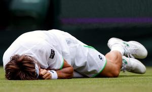 Spain's David Ferrer slips during his match against Argentina's Martin Alund during day Two of the Wimbledon Championships at The All England Lawn Tennis and Croquet Club, Wimbledon. PRESS ASSOCIATION Photo. Picture date: Tuesday June 25, 2013. See PA story TENNIS Wimbledon. Photo credit should read: Jonathan Brady/PA Wire. RESTRICTIONS: Editorial use only. No commercial use. No video emulation. No use with any unofficial third party logos.
