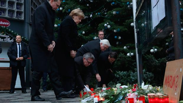 BERLIN, GERMANY - DECEMBER 20:   (L-R) Mayor of Berlin, Michael Muller, German Chancellor Angela Merkel, German Interior Minister Thomas de Maiziere and Forign Minister Frank-Walter Steinmeier lay flowers near where yesterday a lorry ploughed through a Christmas market on December 20, 2016 in Berlin, Germany. So far 12 people are confirmed dead and 45 injured. Authorities have confirmed they believe the incident was an attack and have arrested a Pakistani man who they believe was the driver of the truck and who had fled immediately after the attack. Among the dead are a Polish man who was found on the passenger seat of the truck. Police are investigating the possibility that the truck, which belongs to a Polish trucking company, was stolen yesterday morning.(Photo by Sean Gallup/Getty Images)