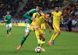 Northern Ireland's Kyle Lafferty (rear) tussles with Romania's Vlad Chiriches during the UEFA Euro 2016 qualifier at the Arena Nationala, Bucharest. Nick Potts/PA Wire.