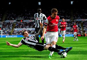 NEWCASTLE UPON TYNE, ENGLAND - MAY 19:  Mathieu Debuchy of Newcastle in action against Aaron Ramsey of Arsenal during the Barclays Premier League match between Newcastle United and Arsenal at St James' Park on May 19, 2013 in Newcastle upon Tyne, England. (Photo by Stu Forster/Getty Images)