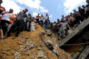Palestinians on the rubble of a home destroyed by an Israeli strike in Khan Younis in the southern Gaza Strip, Friday, July 25, 2014. (AP Photo/Hatem Moussa)