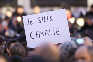 Signs saying 'Je suis Charlie' are held up as crowds gather at 'Place de la Republique' for a vigil following the terrorist attack on January 7, 2015 in Paris