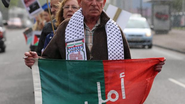 "Activist Phil McCullagh holds a sign reading ""Hope"" in Arabic as crowds attend a white line picket on the Falls Road in Belfast organized by the Belfast Friends of Palestine in opposition to the Israeli Bombing of Gaza. PRESS ASSOCIATION Photo. Picture date: Monday July 14, 2014. Photo credit should read: Niall Carson/PA Wire"