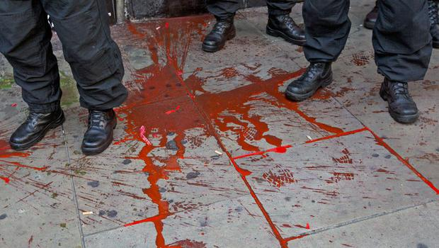 Police officers stand in red paint which was thrown during a rally outside the Israeli Embassy to oppose Israel's actions in Gaza on July 19, 2014 in London, England.  (Photo by Tristan Fewings/Getty Images)