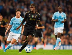 Juventus' midfielder from France Paul Pogba (C) holds off Manchester City's French midfielder Samir Nasri during a UEFA Champions League group stage football match between Manchester City and Juventus at the Etihad stadium in Manchester, north-west England on September 15, 2015.    AFP PHOTO / PAUL ELLISPAUL ELLIS/AFP/Getty Images