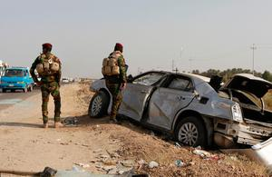 Iraqi government forces stand next to a damaged vehicle at the site of car bomb explosion targeting an Iraqi army checkpoint in Yusufiya, south of the capital Baghdad, on October 17, 2016. The attack came just hours after Iraqi forces launched an offensive to retake second city Mosul, in the north of the country, from the Islamic State group. / AFP PHOTO / SABAH ARARSABAH ARAR/AFP/Getty Images