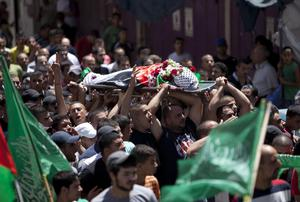 Palestinians carry the body of Mohammed al-Araj during his funeral in the Qalandia refugee camp near the West Bank city of Ramallah, Friday, July 25, 2014. (AP Photo/Majdi Mohammed)