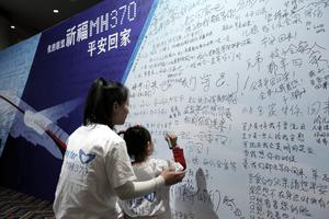 BEIJING, CHINA - MARCH 22: A Chinese girl and her mother of a passenger from the missing Malaysia Airlines flight MH370 writing clifford slogans board at the Lido Hotel on March 22, 2014 in Beijing China. The search to identify whether two large objects spotted via satellite in the Indian Ocean are related to missing flight MH370 continues today, for the third day, with no results. The airliner went missing nearly two weeks ago carrying 239 passengers and crew on route from Kuala Lumpur to Beijing.  (Photo by Lintao Zhang/Getty Images)