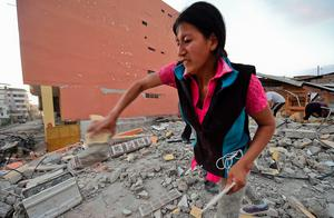 Ecuadorean Veronica Paladines, removes rubble in search for her husband at Tarqui neigbourhood in Manta, Ecuador on April 17, 2016 a fay after a powerful quake hit the country. The toll from the big earthquake in Ecuador rose on Sunday to 246 dead and 2,527 people injured, the country's vice president said. / AFP PHOTO/AFP/Getty Images