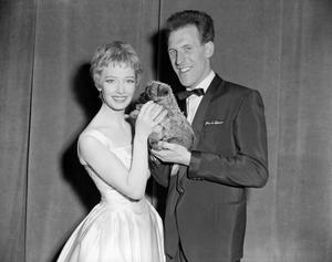 TV star Jeannie Carson receiving a surprise gift, a Cairn terrier puppy, from host Sir Bruce Forsyth after the 'Sunday Night at the London Palladium' show. PA/PA Wire