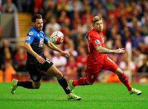 LIVERPOOL, ENGLAND - AUGUST 17:  Adam Smith of Bournemouth and Alberto Moreno of Liverpool chase the ball during the Barclays Premier League match between Liverpool and A.F.C. Bournemouth at Anfield on August 17, 2015 in Liverpool, United Kingdom.  (Photo by Alex Livesey/Getty Images)