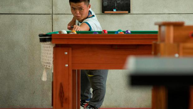 China's Wang Wei plays billiard at the Paralympic Village during the Paralympic Games in Rio de Janeiro, Brazil, on September 6, 2016. Photo by: Al Tielemans /OIS/IOC via AFP.  RESTRICTED TO EDITORIAL USE. / AFP PHOTO / OIS/IOC / Al Tielemans for OIS/IOCAL TIELEMANS FOR OIS/IOC/AFP/Getty Images