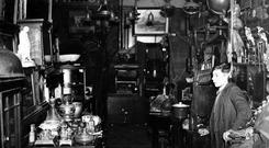 Smithfield market, Belfast.Young boy in a shop selling household furniture lamps and bric a brac. 26/11/1941
