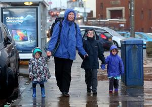Mum Stephanie with children  Fionnan, Alicia, Lara Hodge walking home from school in the rain close to Portstewart harbour. Pic Kevin Scott