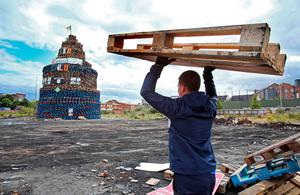 A wooden pallet is carried to a bonfire in the Shankill area of west Belfast, Northern Ireland on July 10, 2017, ahead of the traditional 11th night bonfires  [Photo: Paul Faith /AFP/Getty Images]