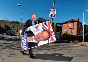 Democratic Unionist Party Deputy Leader, Nigel Dodds carries a large poster as he canvasses for the general election on April 18, 2015 in Belfast, Northern Ireland. (Photo by Charles McQuillan/Getty Images)