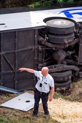 A police officer points to the underside of a bus as he attends to the scene of the crash on a motorway in Middlekerke, Belgium on Sunday. (AP Photo/Geert Vanden Wijngaert)