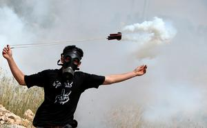 A Palestinian protester throws back a tear gas cannister using a sling shot during clashes with Israeli security forces on April 17, 2015 following a demonstration marking Palestinian Prisoner Day in the West Bank town of Bilin, near Ramallah. AFP/Getty Images