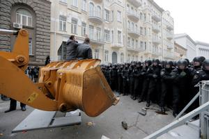 Protesters on excavator  call to police go away during clash with police at Presidential office in Kiev, Ukraine, on Sunday, Dec. 1, 2013. As many as 100,000 demonstrators chased away police to rally in the center of Ukraine's capital on Sunday, defying a government ban on protests on Independence Square, in the biggest show of anger over the president's refusal to sign an agreement with the European Union. (AP Photo/Efrem Lukatsky)