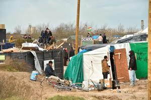"Migrants stand next to shelters on February 29, 2016 in the ""jungle"" migrants and refugees camp in Calais, northern France as workers dismantle the southern half of the sprawling camp in the port town. Pic Getty Images"