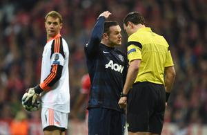 MUNICH, GERMANY - APRIL 09:  Wayne Rooney of Manchester United talks to referee Jonas Eriksson watched by Manuel Neuer of Bayern Muenchen during the UEFA Champions League Quarter Final second leg match between FC Bayern Muenchen and Manchester United at Allianz Arena on April 9, 2014 in Munich, Germany.  (Photo by Lars Baron/Bongarts/Getty Images)