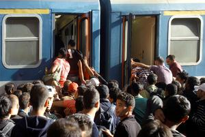 Migrants board into a local train heading to the Hungarian-Austrian border at the main train station in Budapest on September 3, 2015, after authorities re-opened the station to refugees. On the day before Hungarian authorities stopped migrants taking trains to Austria and Germany.  AFP PHOTO / PETER KOHALMIPETER KOHALMI/AFP/Getty Images