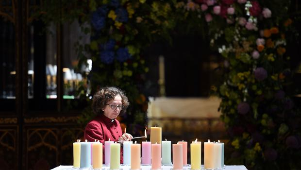 A member of the clergy lights candles for the victims (Paul Ellis/PA)