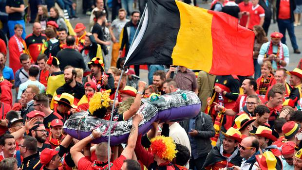 Belgium's supporters carry another one in a inflatable boat next to a Belgium's flag at the main square, La Grand Place, in Lille on July 1, 2016 ahead of the Euro 2016 football tournament quarter final match between Belgium and Wales. / AFP PHOTO / PHILIPPE HUGUENPHILIPPE HUGUEN/AFP/Getty Images