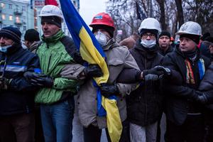 KIEV, UKRAINE - DECEMBER 8: Anti-government protesters lock arms to block access to a street that leads to the Ukrainian parliament building, the site of a rally held by the ruling Party of Regions in support of the government and Ukrainian president Viktor Yanukovych, on December 8, 2013 in Kiev, Ukraine. Thousands of people have been protesting against the government since a decision by President Yanukovych to suspend a trade and partnership agreement with the European Union in favor of incentives from Russia. (Photo by Brendan Hoffman/Getty Images)