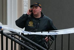 A Garda outside the Regency Hotel in Dublin after one man died and two others were injured following a shooting incident at the hotel. PA