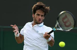 LONDON, ENGLAND - JUNE 25:  Feliciano Lopez of Spain plays a forehand during his Gentlemen's Singles first round match against Gilles Simon of France on day two of the Wimbledon Lawn Tennis Championships at the All England Lawn Tennis and Croquet Club on June 25, 2013 in London, England.  (Photo by Clive Brunskill/Getty Images)