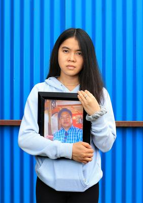 Mikee Plangca (21) holds a photograph of her father Miguel who was a factory worker and lost his life to Covid-19, leaving Mikee and her 3 siblings orphans. Picture by Frank McGrath