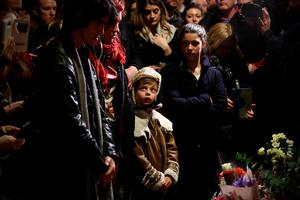 LONDON, ENGLAND - JANUARY 11: A boy looks up as members of the public gather and lay flowers by a mural of David Bowie in Brixton on January 11, 2016 in London, England. British music and fashion icon David Bowie died earlier today at the age of 69 after a battle with cancer.  (Photo by Carl Court/Getty Images)