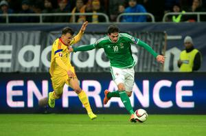 Northern Ireland's Kyle Lafferty (right) and Romania's Vlad Chiriches battle for the ball during the UEFA Euro 2016 qualifier at the Arena Nationala, Bucharest. Nick Potts/PA Wire.