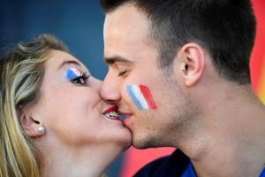 France supporters kiss as they wait for the start of the Euro 2016 semi-final football match between Germany and France at the Stade Velodrome in Marseille on July 7, 2016.  / AFP PHOTO / FRANCK FIFEFRANCK FIFE/AFP/Getty Images