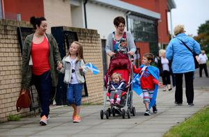 GLASGOW, SCOTLAND - SEPTEMBER  18:  (L-R) Angela Simpson, Niamh Cupples, Ava Cupples (buggy), Linda Cupples and Calum Cupples leave St Bartholomew's Primary School in Castlemilk after casting their vote as the people of Scotland take to the poles to decide their country's fate in a historic vote on September 18, 2014 in Glasgow, Scotland. After many months of campaigning the people of Scotland today head to the polls to decide the fate of their country. The referendum is too close to call but a Yes vote would see the break-up of the United Kingdom and Scotland would stand as an independent country for the first time since the formation of the Union. (Photo by Mark Runnacles/Getty Images)