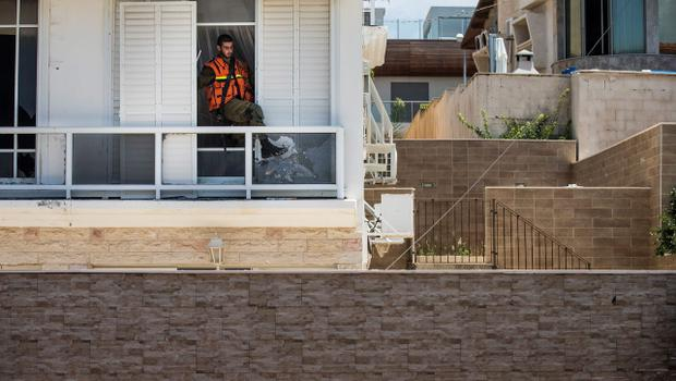 "ASHDOD, ISRAEL - JULY 15:  A Homefront Command member clears shattered glass from a frame after a Hamas rocket landed across the street on July 15, 2014 in Ashdod, Israel.  As operation 'Protective Edge"" enters it's eighth day of airstrikes by the Israel Defense Forces (IDF) across the Gaza Strip, Egypt has this morning tabled a ceasefire agreement proposing a halting of fighting starting at 9am. Once violence has ceased, the proposal calls for Israel to open a border crossing into Gaza to allow the movement of goods and people. Israel has accepted the Egyptian proposal for a truce, however it is thought Hamas has rejected the deal.  (Photo by Andrew Burton/Getty Images)"