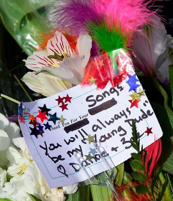 """A written note is seen amid flowers, candles and other mementos placed on the Hollywood Star of the late David Bowie in Hollywood, California, on January 11, 2016.   Bowie died at the age of 69 after a secret battle with cancer, prompting a cascade of tributes for one of the most influential and innovative artists of his time. A notoriously private person, Bowie's death was a shock with his death coming just two days after he released his 25th studio album """"Blackstar"""", on his 69th birthday on January 8. """"David Bowie died peacefully today (Sunday) surrounded by his family after a courageous 18-month battle with cancer,"""" said a statement posted January 11 on his official social media accounts.  AFP PHOTO/FREDERIC J. BROWNFREDERIC J. BROWN/AFP/Getty Images"""