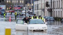 PSNI officers help a driver move his flooded car from Bridge Street in Newry.