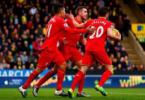 NORWICH, ENGLAND - JANUARY 23: Roberto Firmino (L) of Liverpool ceelbrates scoring his team's third goal with his team mates Jordan Henderson (C) and Adam Lallana (R) during the Barclays Premier League match between Norwich City and Liverpool at Carrow Road on January 23, 2016 in Norwich, England.  (Photo by Clive Mason/Getty Images)