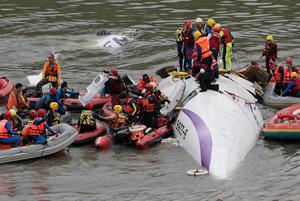 Emergency personnel try to extract passengers from a commercial plane after it crashed in Taipei, Taiwan, Wednesday, Feb. 4, 2015. The Taiwanese commercial flight with 58 people aboard clipped a bridge shortly after takeoff and crashed into a river in the island's capital of Taipei on Wednesday morning.  A Taiwanese flight with 58 people aboard went sideways, clipped an elevated roadway and careened into a river Wednesday shortly after takeoff from the island's capital of Taipei. (AP Photo/Wally Santana)