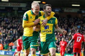 Norwich City's Irish midfielder Wes Hoolahan (R) celebrates with Norwich City's Scottish striker Steven Naismith (L) after scoring their third goal during the English Premier League football match between Norwich City and Liverpool at Carrow Road in Norwich, eastern England, on January 23, 2016. Liverpool won the game 5-4. AFP PHOTO / LINDSEY PARNABY  RESTRICTED TO EDITORIAL USE. No use with unauthorized audio, video, data, fixture lists, club/league logos or 'live' services. Online in-match use limited to 75 images, no video emulation. No use in betting, games or single club/league/player publications.LINDSEY PARNABY/AFP/Getty Images
