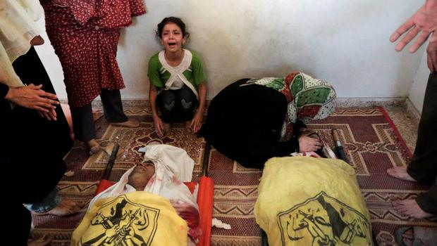 Palestinians cry around the bodies of Shaher al-Najar, left, and his brother Bassem al-Najar, right, killed in an Israeli strike, at the family house during their funeral in Jebaliya refugee camp, northern Gaza Strip, Wednesday, July 30, 2014 (AP Photo/Lefteris Pitarakis)